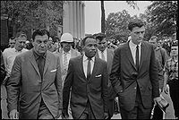 James Meredith walking to class at the University of Mississippi, accompanied by U.S. Marshals.