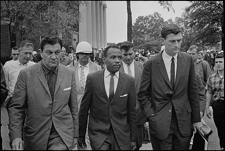 James Meredith walking to class at the University of Mississippi, accompanied by U.S. Marshals James Meredith OleMiss.jpg