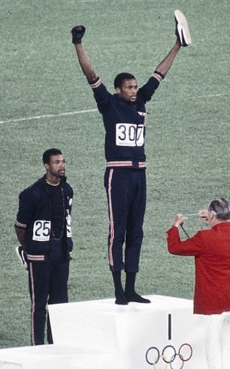 Tommie Smith - John Carlos and Tommie Smith (center) at the 200 m award ceremony of the 1968 Olympics, wearing black gloves, black socks and no shoes