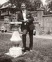 John McCrae leaning against a sundial