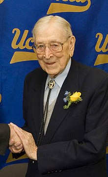 John Wooden at his 96th birthday ceremony in a black suit with a yellow flower attached on the left with UCLA printed cloth hanging behind him.