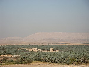 View o Kharga Oasis wi the Temple o Hibis in the centre an the desert cliffs at the top