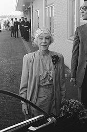 souriante, Élisabeth vêtue d'un tailleur clair pose près d'une voiture devant les bâtiments d'un aéroport