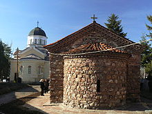 An Orthodox monastery courtyard with a small medieval church to the right and a more modern one to the left
