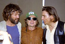 Three men. From left to right, the first man has brown hair and beard. He wears a blue t-shirt and a white jacket and is looking at the man in the middle. The man in the middle wears a green cap and shades, and long red hair. He wears a brown t-shirt. The man at the right has brown hair, he looks at the man at the middle. He wears a white shirt and a black letter jacket.