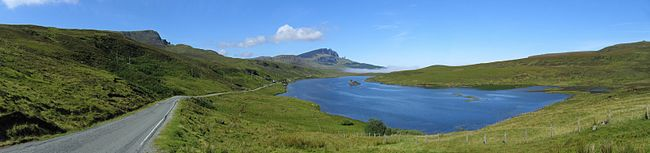 A blue body of water sits beneath a blue sky surrounded by green moorland. A road to the left travels along the lake side leading towards a small patch of mist and some low hills in the distance.