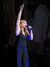 A blond woman singing into a microphone in her left hand, while pointing her right hand upwards. She is dressed in black trousers with a black, sleeveless jacket. Her hair falls in curls around her, but is set in place by a black band.