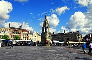 """Mansfield Market Place with the <a href=""""http://search.lycos.com/web/?_z=0&q=%22Lord%20George%20Bentinck%22"""">Bentinck</a> Memorial rising above the market stalls"""