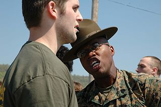 Sergeant Paul Nixon, drill instructor, 3rd Recruit Training Battalion, Marine Corps Recruit Depot Parris Island, South Carolina, gives a poolee some added incentive to do what he's told. Approximately 400 future Marines gathered May 7, 2005 at Fort Indian Town Gap, Pennsylvania, for Recruiting Station Harrisburg's Annual Future Marine Challenge. The purpose of the event is to familiarize the future Marines with boot camp and to allow them to learn about teamwork and camaraderie. (original caption) Date07.05.2005 Sourcewww.usmc.mil images AuthorStaff Sergeant J.L. Wright Jr. via Wikimedia Commons