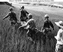 Several men carry a man on a stretcher through a field of grass