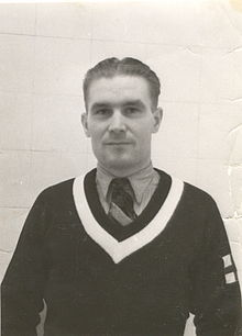 A photograph of a Caucasian man, wearing a sweater over a shirt and tie. He is pictured against a white tiled wall.