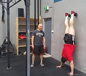 CrossFit - The wall walk exercise uses a wall to practice handstands, usually used as skill work to strengthen the shoulder and core in order to improve overhead movements and handstand push ups.