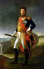 Formal full-length portrait of Soult in uniform, in a coastal landscape with military barracks and beacon post. He is a sturdily built man with swarthy skin, short black hair, a cleft chin and prominent ears. Both his facial expression and his stance express arrogance. He holds a marshal's baton and hat.