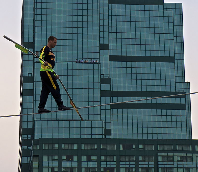 A man tightrop walks with a large building in the background