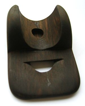 Nose whistle - A rosewood nose whistle. The player puts one's nose on the upper hole. The air is directed towards the lower edge, where the open mouth makes the sound.