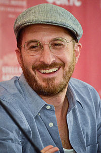 Darren Aronofsky kneeling while holding a microphone