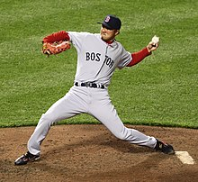 "man wearing a grey baseball uniform that says ""BOSTON"" in navy letters clutches a baseball behind his head with his left hand as he prepares to throw it."