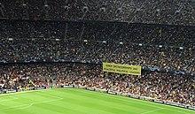 """Una sezione delle tribune in uno stadio di calcio, con una folla numerosa.  In basso è visibile un angolo del campo.  Un grande striscione giallo è appeso al secondo livello degli spalti, con la scritta """"Solo le dittature imprigionano i leader politici pacifici"""" (in inglese) in stampatello."""