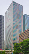 Ground-level view of a brown, rectangular, window-dotted high-rise; there are darker square patches placed randomly along the building's facades