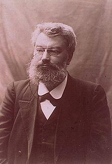 Foto monocromática de um homem barbudo usando um monóculo.