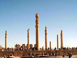 Photograph a large terrace nearly 4 meters thick supporting several columns of up to 20 meters high, some decorated near the top, and with several tens of tourists and a blue sky.