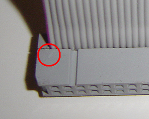 "Insulation-displacement connector - The ""V"" mark (circled) shows the position of pin 1"