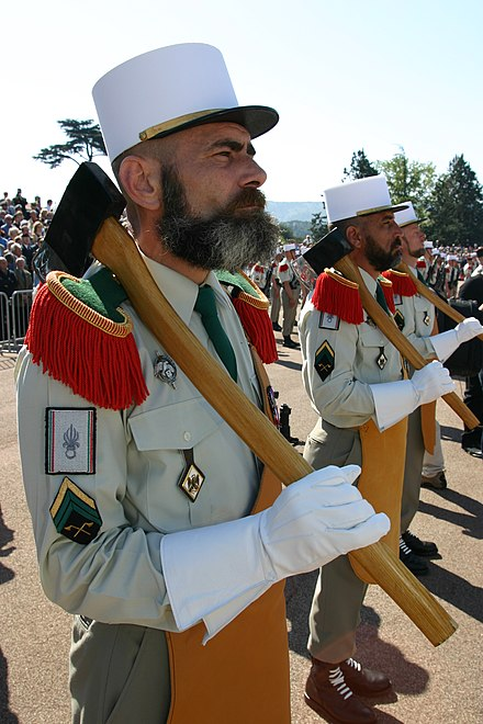 "The sappers (""sapeurs"") of the French Foreign Legion traditionally sport large beards, wear leather aprons and gloves in their ceremonial dress, and carry axes. Pionnier-legion.JPG"
