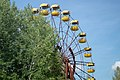 Pripyat Amusement park ferriswheel viewed from behind the tree canopy 2018.jpg