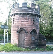 Photograph of a short round brick tower in a central reservation of an English road, the remnants of the abbey's gatehouse