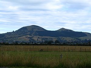 Saddle Hill (New Zealand) - Saddle Hill from the Taieri Plains, showing the shape which gives the hill its name. East to the left.