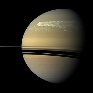 Saturn - A global storm girdles the planet in 2011. The head of the storm (bright area) passes the tail circling around the left limb.