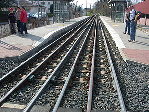Gauntlet track - Triple gauntlet track at Kaufungen, Germany. Wider mainline trains go down the centre; narrower trams switch either to the left, or right, to be closer to the relevant platform. Beyond the station, the rails return to single track.