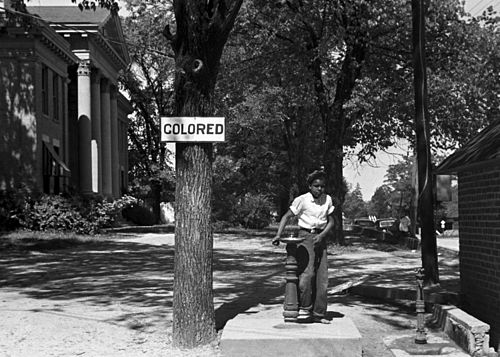 An African-American child at a segregated drinking fountain on a courthouse lawn, North Carolina, US 1938. Segregation 1938b.jpg