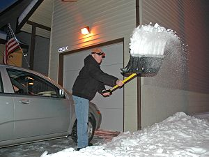 Staff Sgt. Phillip Bridges shovels the drivewa...