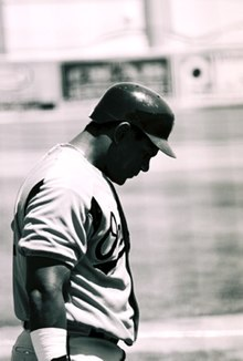 A dark skinned man in a white baseball uniform. His face is partially obscured by the shadow of his batting helmet.