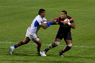 Stiff-arm fend - Fend by Edwin Maka during a rugby union game.