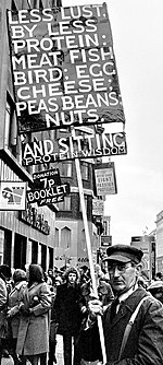 "A man in coat, tie, glasses, and a baseball-like cap carries a tall sign in a crowded street. The sign says ""LESS LUST, BY LESS PROTEIN: MEAT FISH BIRD; EGG CHEESE; PEAS BEANS; NUTS."" Then ""AND SITTING"", and in smaller letters below that, ""PROTEIN WISDOM""."