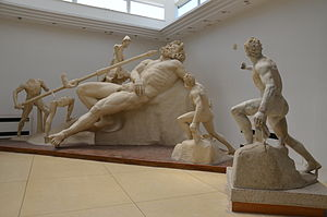 """Sperlonga sculptures - The central group at Sperlonga, with the Blinding of Polyphemus; cast reconstruction of the group, with at the right the original figure of the """"wineskin-bearer"""" seen in front of the cast version."""