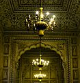 The beautiful interior view with amazing Mughal wall art, enlightened by yellow light of chandelier.jpg