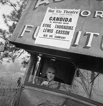 Lewis Casson - Casson drives the Old Vic Travelling Theatre Company scenery van during the Old Vic tour of South Wales in 1941. The van is an old furniture removal van. A poster above the windscreen advertises the play they will be performing as Candida by George Bernard Shaw, starring Casson and Sybil Thorndike, and directed by Tyrone Guthrie.