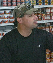 A man with a goatee wearing a black shirt and camouflage baseball cap