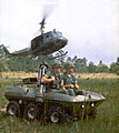 Two-man team with Dragon missile and helicopter behind them.jpg