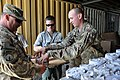 U.S. Army Staff Sgt. Alex Prevett, right, with Combined Joint Interagency Task Force 435, prepares to place newly formed fuel doughnuts on drying racks during an Operation Outreach Afghanistan program at Camp 130728-F-JL359-017.jpg