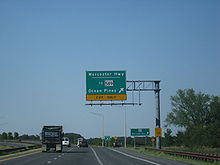 A divided highway curves to the left as the rightmost lane exits underneath an overhead green sign indicating the ramp leads to Worcester Highway and MD 589 toward Ocean Pines