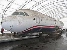 Photo de l'avant du corps de l'avion, dans un grand hangar, avec des traces de boues et d'impact d'oiseaux visibles, notamment avec un trou sur son nez.