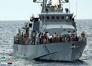 The crew of the coastal patrol ship USS Firebolt (PC 10) tends to some of the 89 survivors rescued from the Gulf of Aden after the small vessel they were traveling in capsized 25 mi (22 nmi; 40 km) off the coast of Somalia on 29 April 2005.