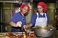 US Navy 030326-N-2143T-001 Mess Management Specialist 3rd Class Andrea Yepez from Saginaw, Mich., and Mess Management Specialist Seaman Lene Jones from Alexandra, La., prepare barbecued chicken for the more than 5,000 Sailors a.jpg