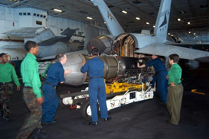 Archivo: US Navy 040615-N-2591H-002 El taller de aviación del Departamento de Mantenimiento Intermedio de Aviación (AIMD, por sus siglas en inglés) reemplaza al motor a reacción Turbo de F404-GE-402 Turbo de General Electric de un Hornet FA-18 luego de reparaciones menores a bordo del USS John F. Kennedy ( CV 6.jpg