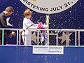 US Navy 040731-N-5258M-003 First Lady Laura Bush christens PCU Texas (SSN 775) with a bottle of champagne as Northrop Grumman Newport News Shipyard President Tom Shievelbein stands by.jpg