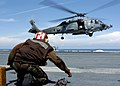 US Navy 050111-N-6817C-162 An Airman prepares to chock and chain a landing HH-60H Seahawk helicopter.jpg